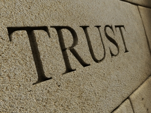 The word TRUST carved into a stone wall. 3D render with HDRI lighting and raytraced textures.